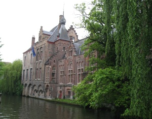 Canal view of Brugge - ancient buildings and lovely greenery in the mist