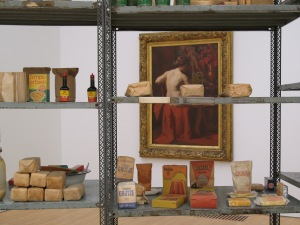 This detail view of the installation shows the classic art seen through the shelving and its contents