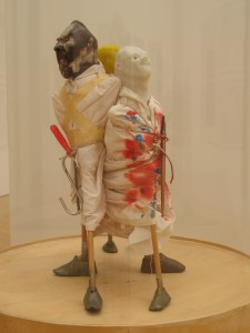 Sculpture: three grotesques holding a pencil, a paint brush and a screwdriver