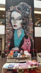 A wall mural in a local bookstore made entirely of books, painted with this woman and her pink kitty.