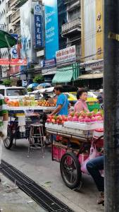Colorful rolling carts displaying fruit in Bangkok's Chinatown
