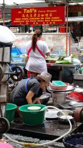 Woman washing pans in a food stall