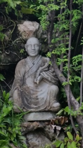 A charming monk figure sits nestled in some greenery