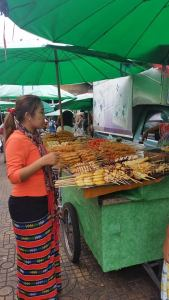 A woman looks over her choices of grilled meats at a street vendor's stall