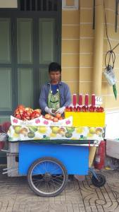 A young man selling freshly made pomegranate juice near Wat Pho.