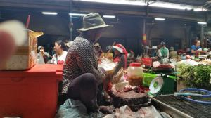 Woman chopping raw fish - right in the center of the Siem Reap market